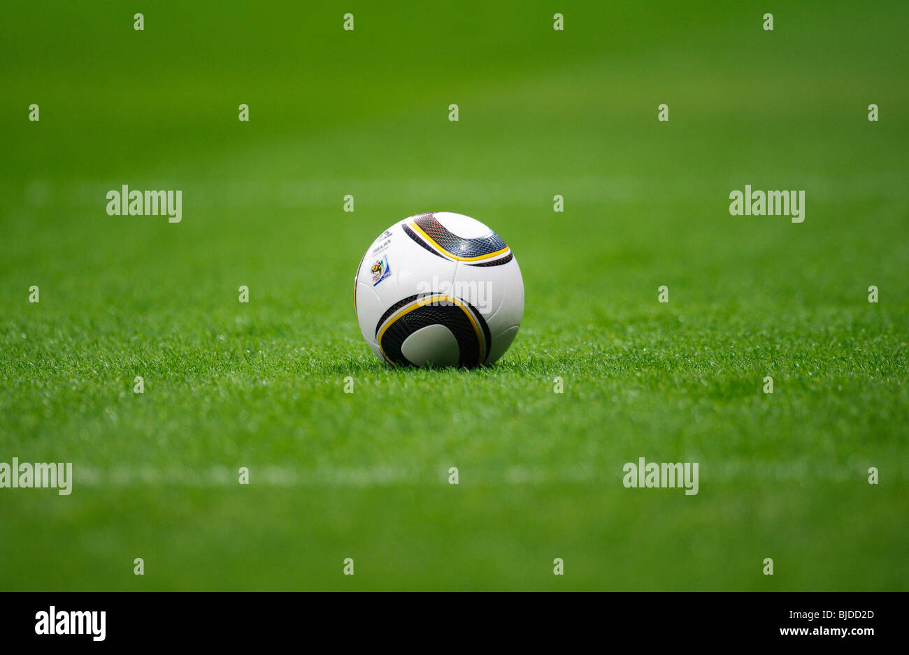Jabulani, official matchball of th FIFA Football World Cup 2010 in South Africa on  green pitch - Stock Image