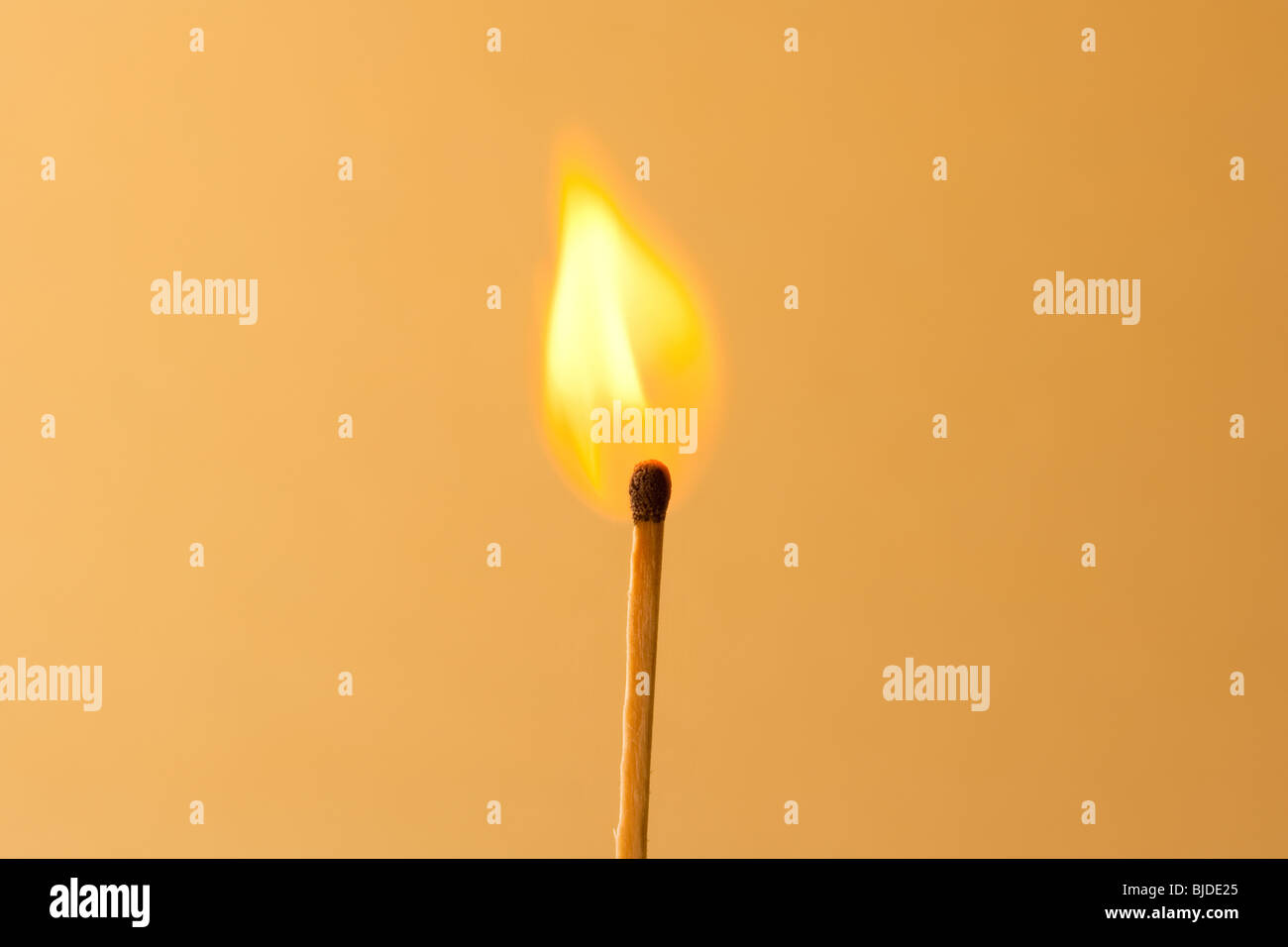Burning Match against an orange background - Stock Image