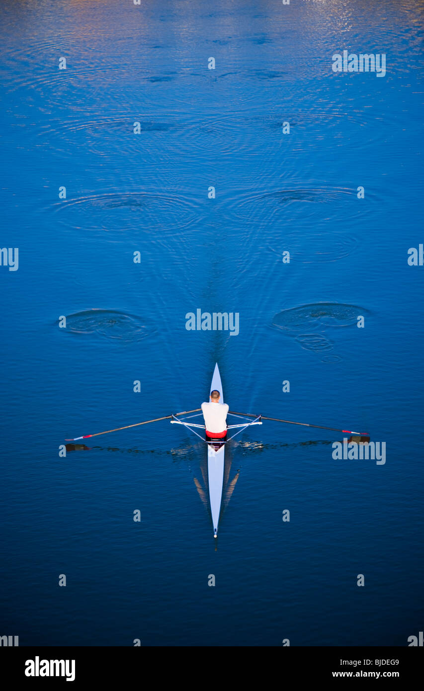 Man rowing on a body of water. - Stock Image