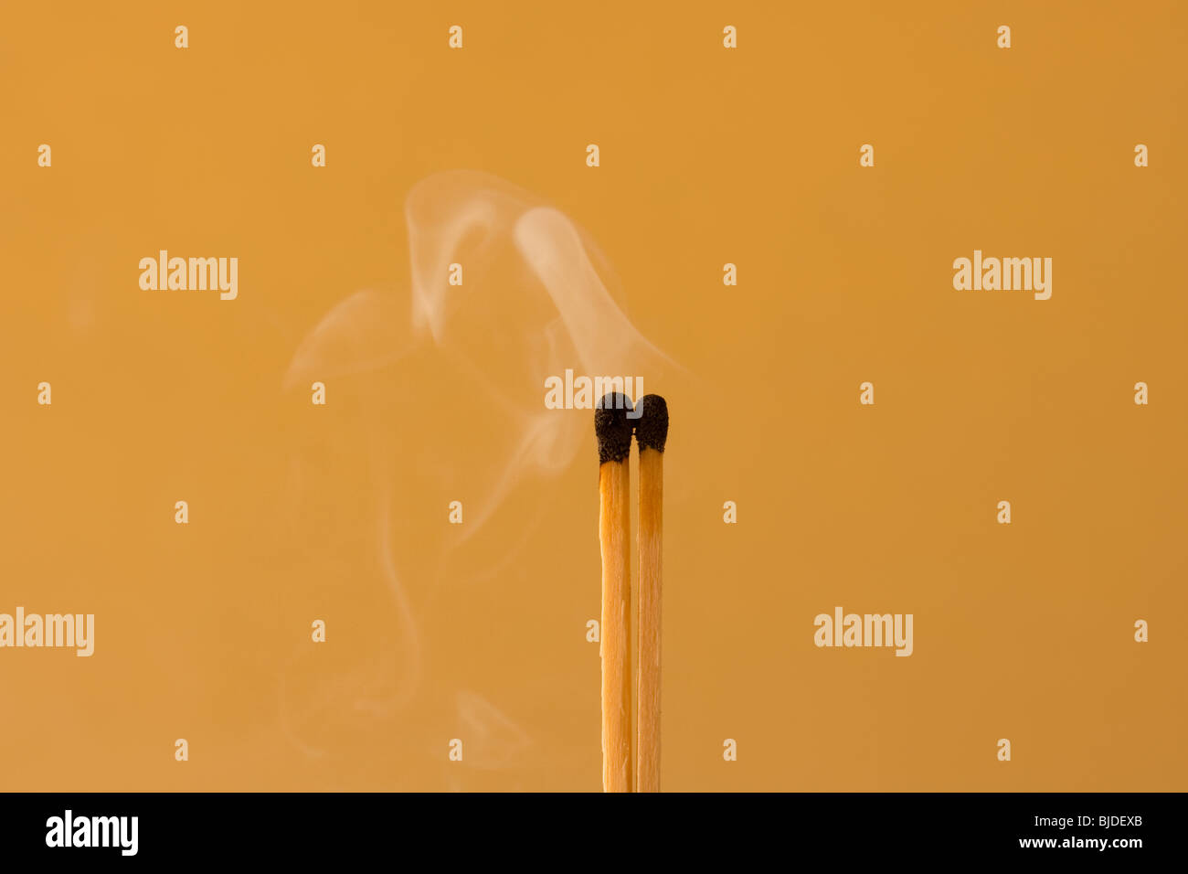 Burn out matches against an orange background - Stock Image
