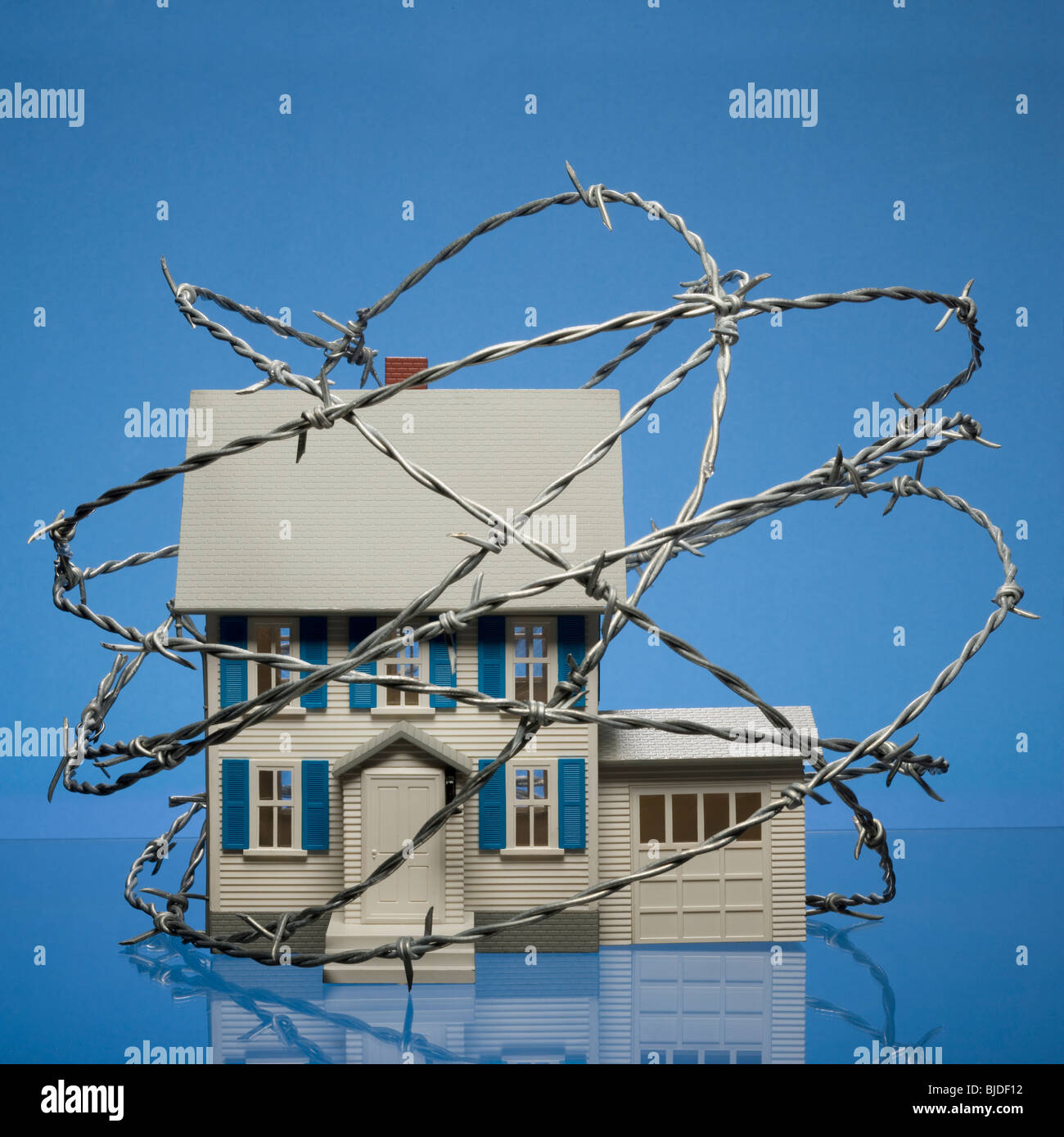 Home surrounded by barbed wire. - Stock Image