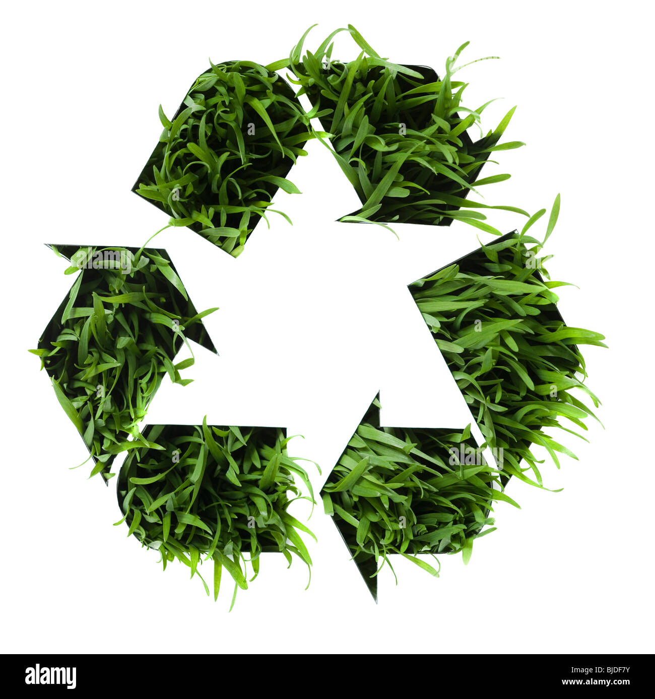 Recycling symbol with grass growing in it. - Stock Image
