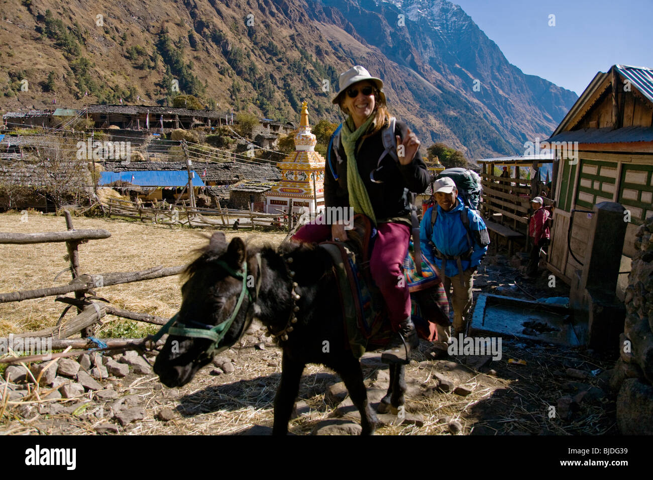 Christine Kolisch rides a horse through the village of LHO on the Around Manaslu Trek - NUPRI REGION, NEPAL - Stock Image