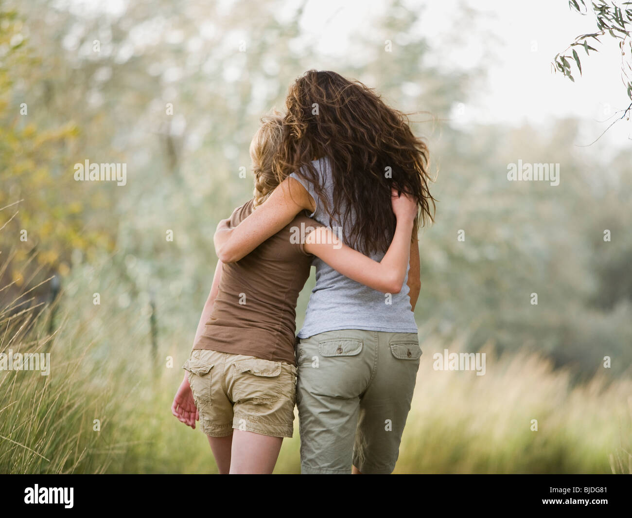 woman and young woman walking with arm around each other. - Stock Image