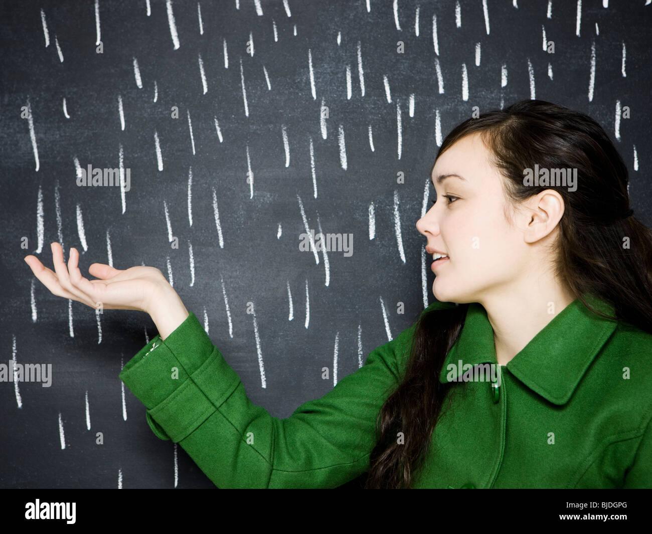 woman in a chalkboard rainstorm - Stock Image