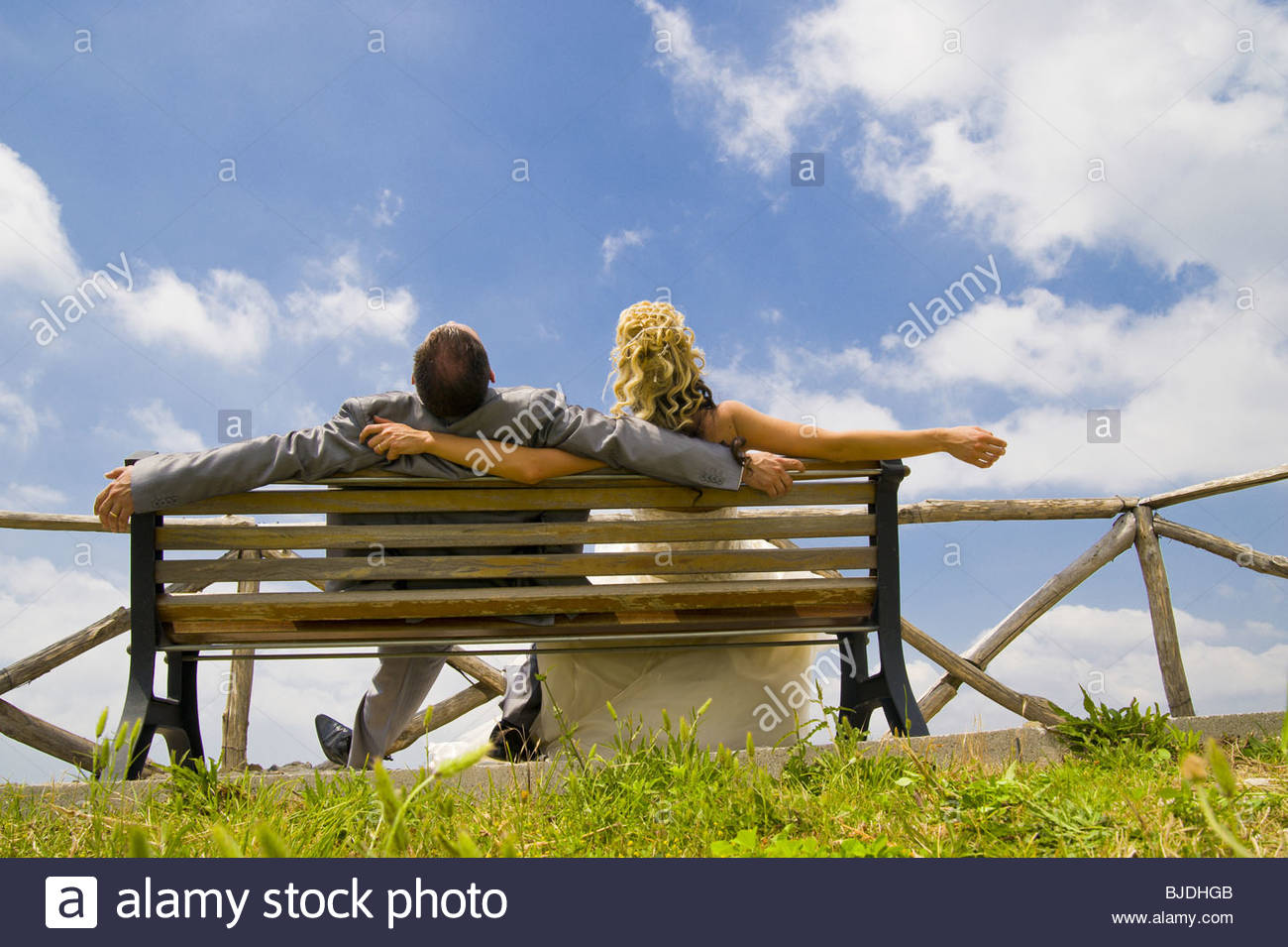 Bride and groom laying back on bench looking at the sky - Stock Image