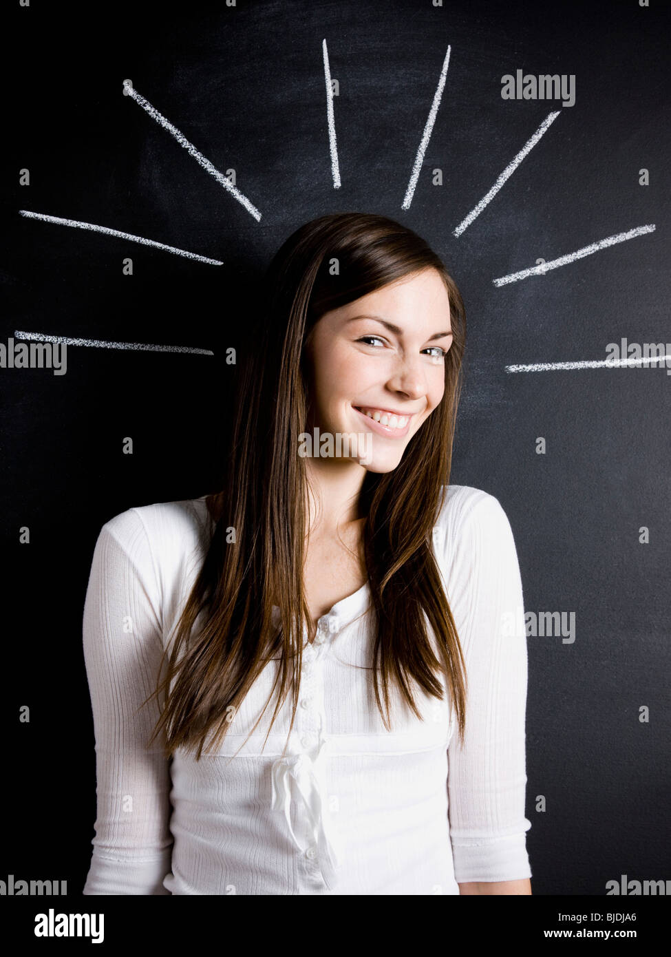 young woman against a chalkboard - Stock Image
