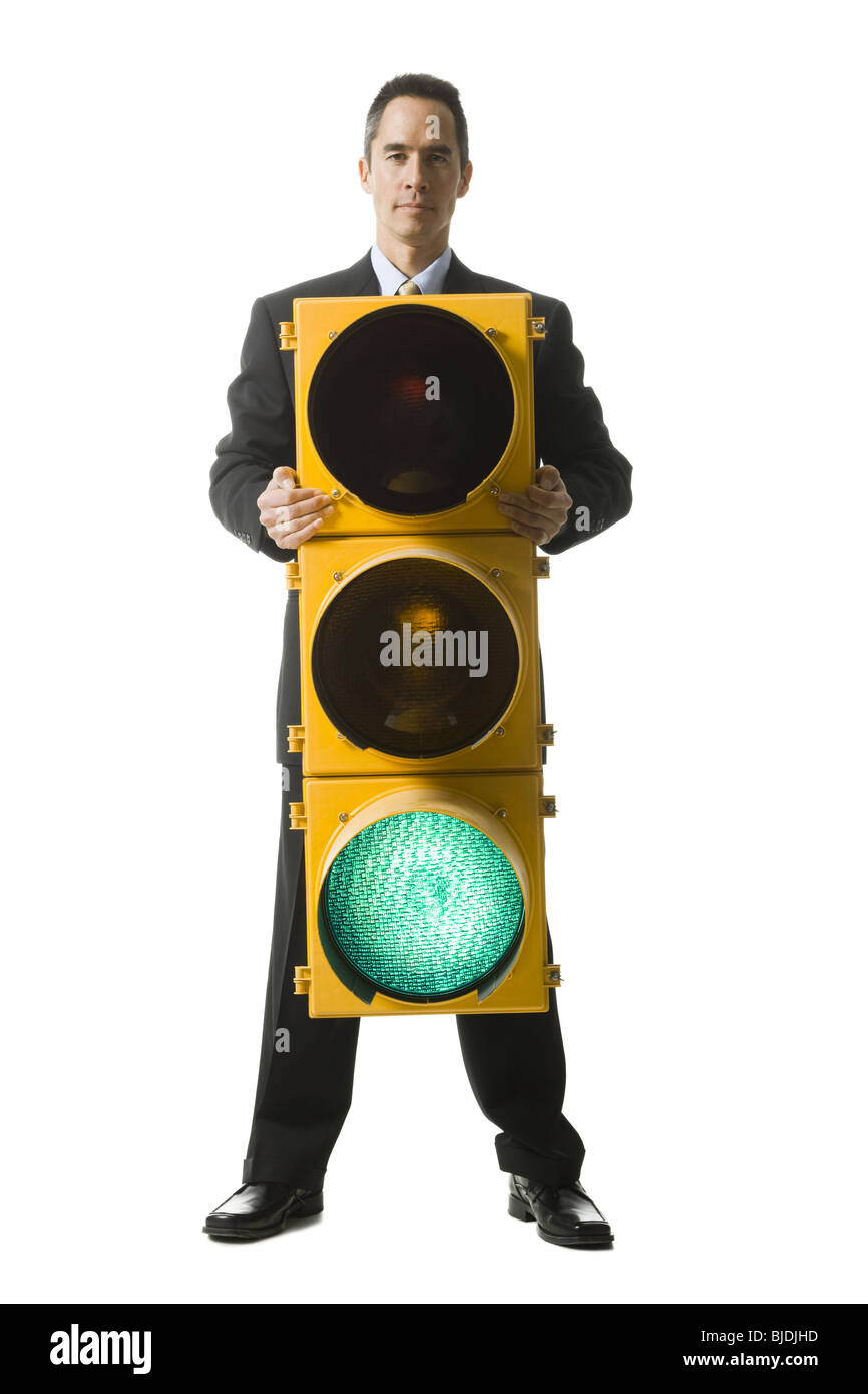 businessperson holding a traffic signal - Stock Image
