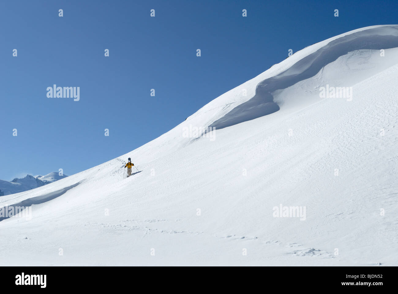 Snowboarder hiking with snow shoes carrying his board in off-piste terrain, Chamonix, France - Stock Image