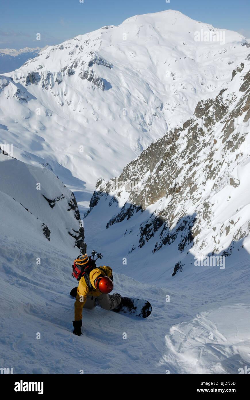 Snowboarder entering very steep gully at Col Belvede, near Le Brevent-Flegere ski resort, Chamonix, France. Mt Buet - Stock Image