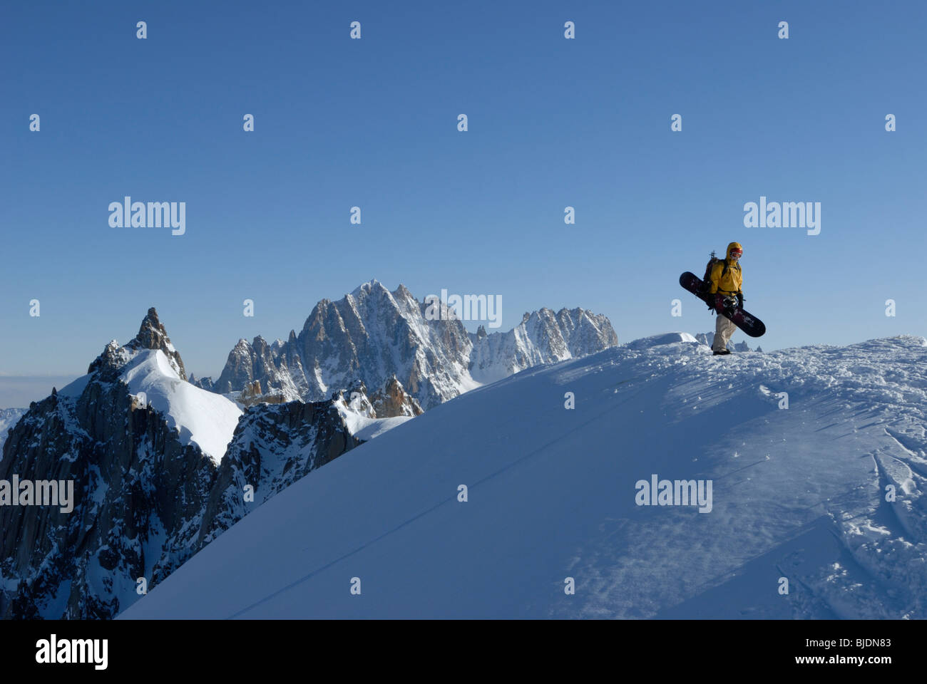 Snowboarder walking on lofty mountain ridge above Vallee Blanche on Aiguille du Midi, Chamonix, France - Stock Image