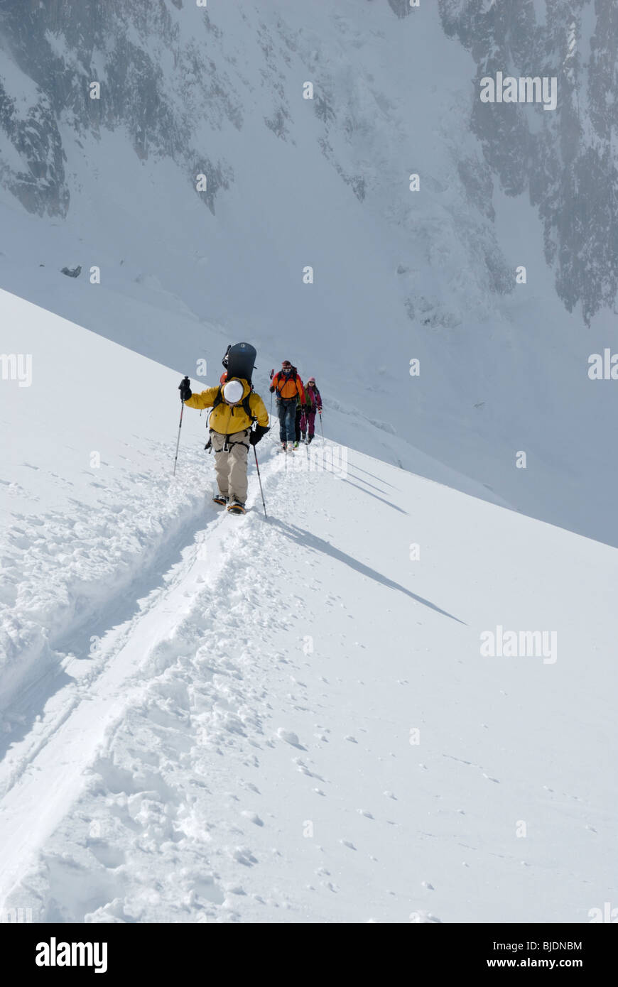 Snowboarder and skiers ascending a snowy slope in glaciated terrain above The Vallee Blanche, Chamonix, France - Stock Image