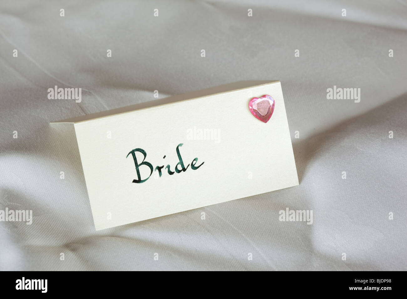 hand written brides table place setting with pink glass heart - Stock Image
