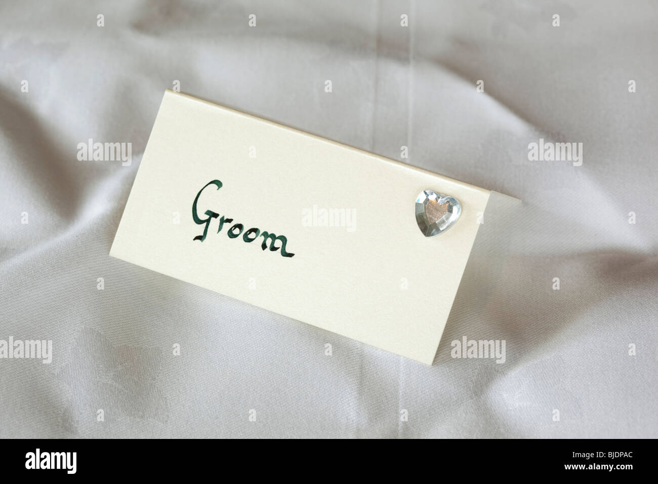 Hand written card grooms table place setting with tiny glass heart, on wedding party table - Stock Image