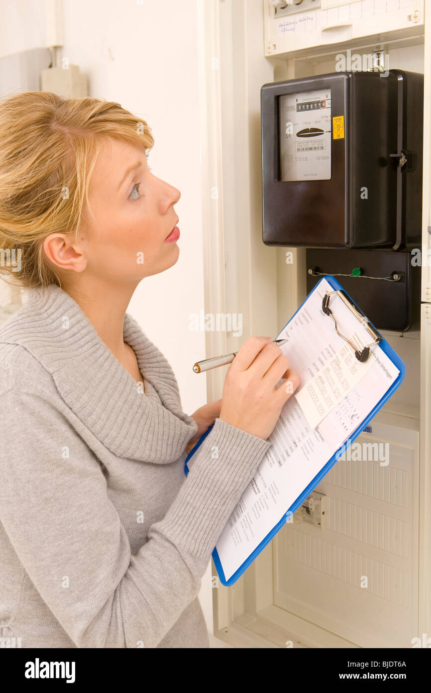 Woman reading the electric meter - Stock Image