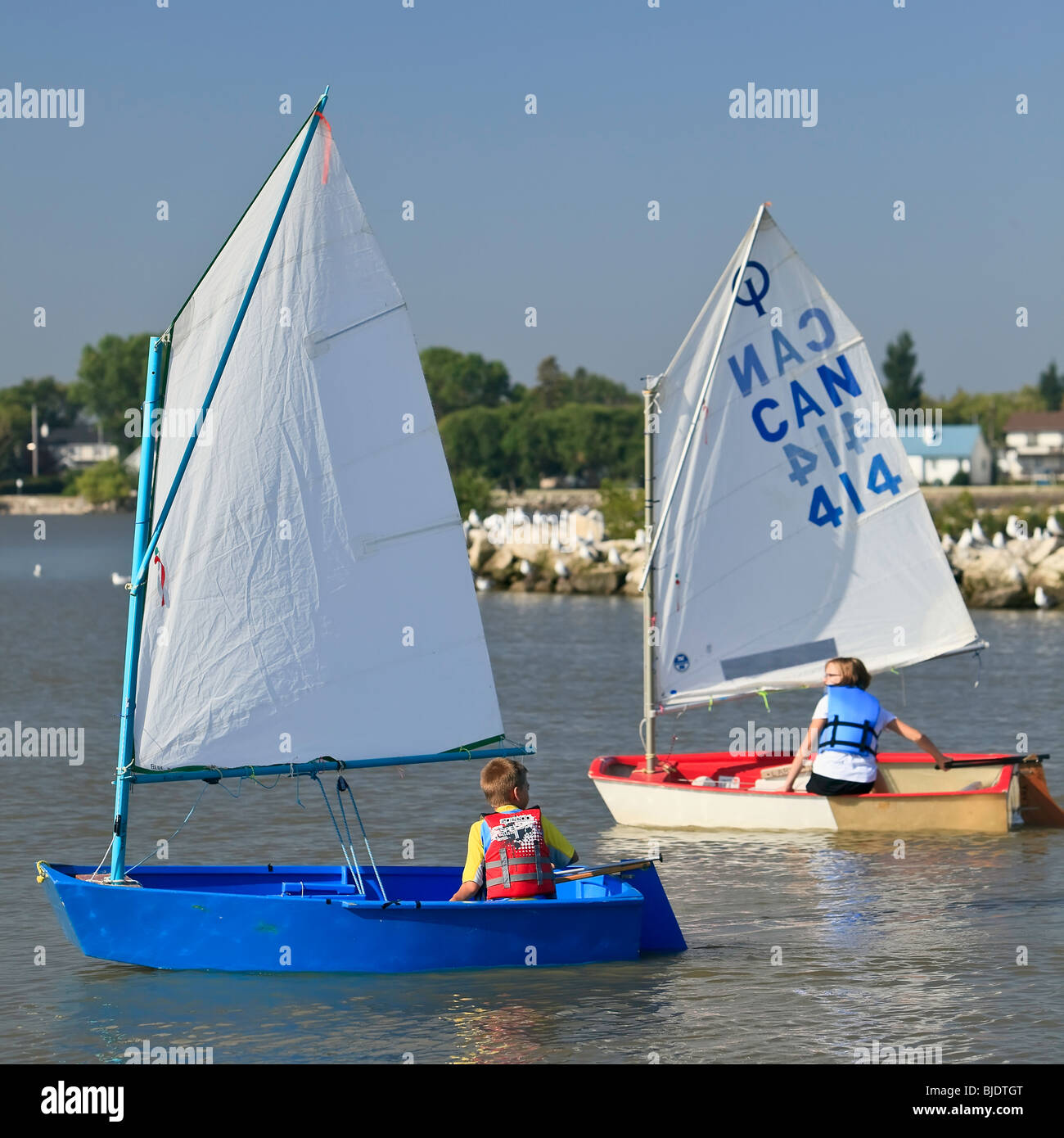 Young boy and girl learning to sail on Lake Winnipeg, Gimli, Manitoba, Canada - Stock Image