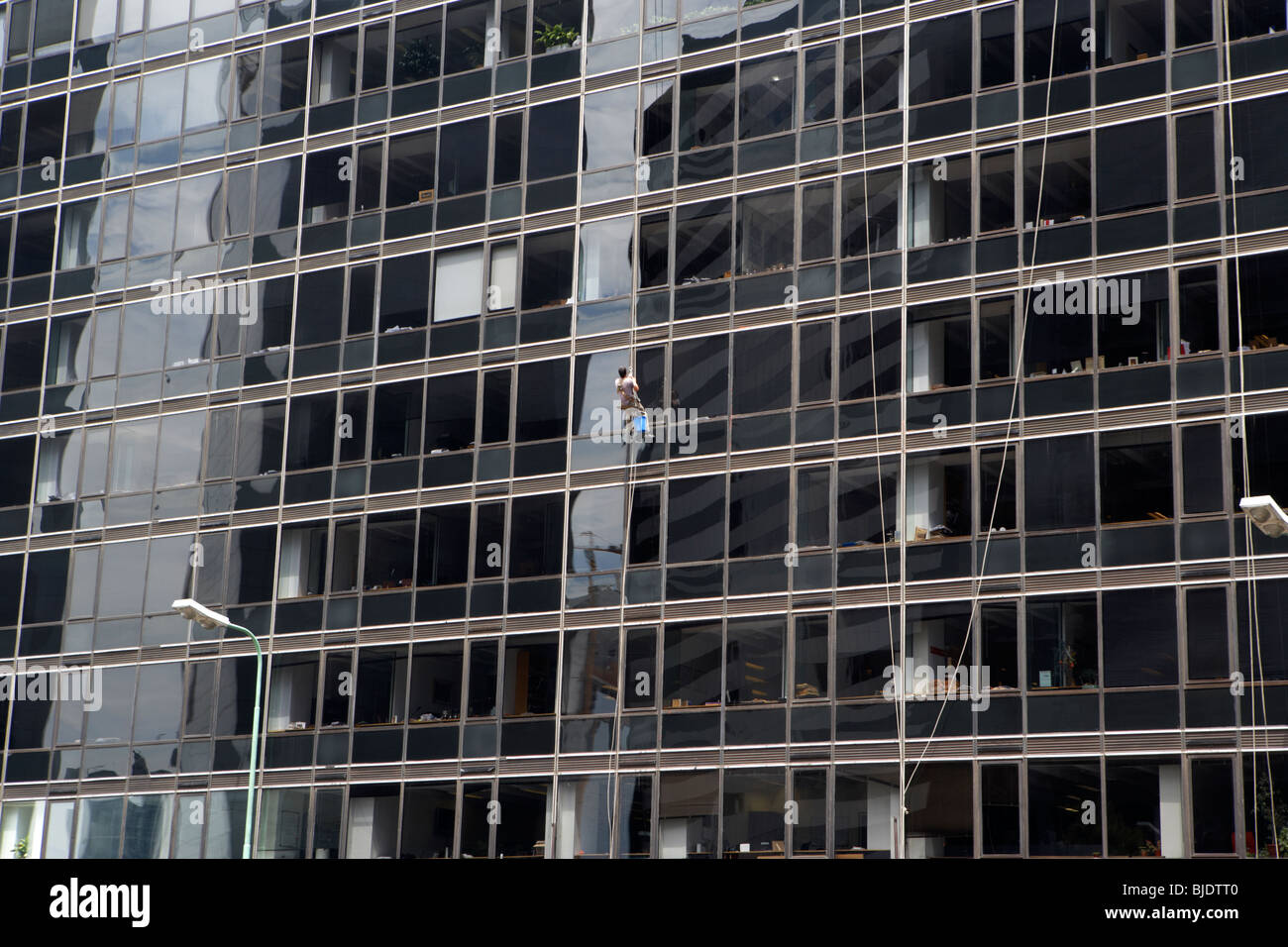man using abseil ropes to clean windows of an office building in the microcentre financial district capital federal - Stock Image