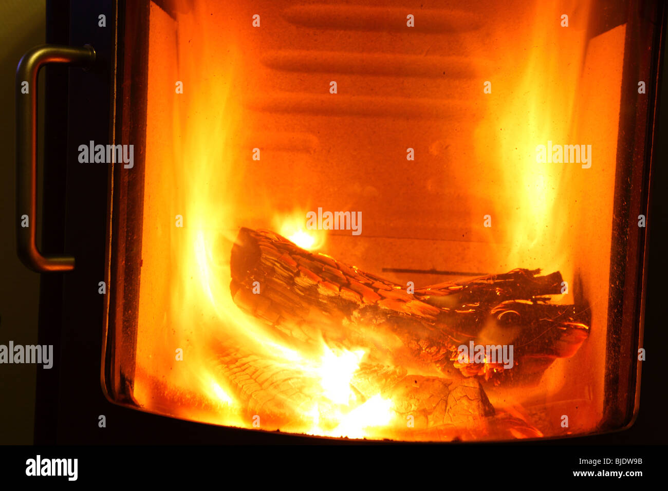 fire place burning wood log stove inside house in winter - Stock Image
