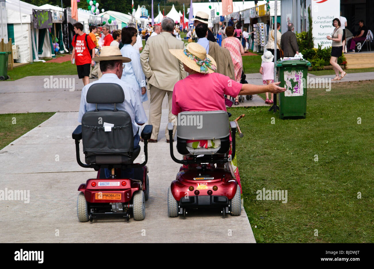 Man and woman on disability scooters at National Eisteddfod of Wales Newport Gwent South Wales UK - Stock Image