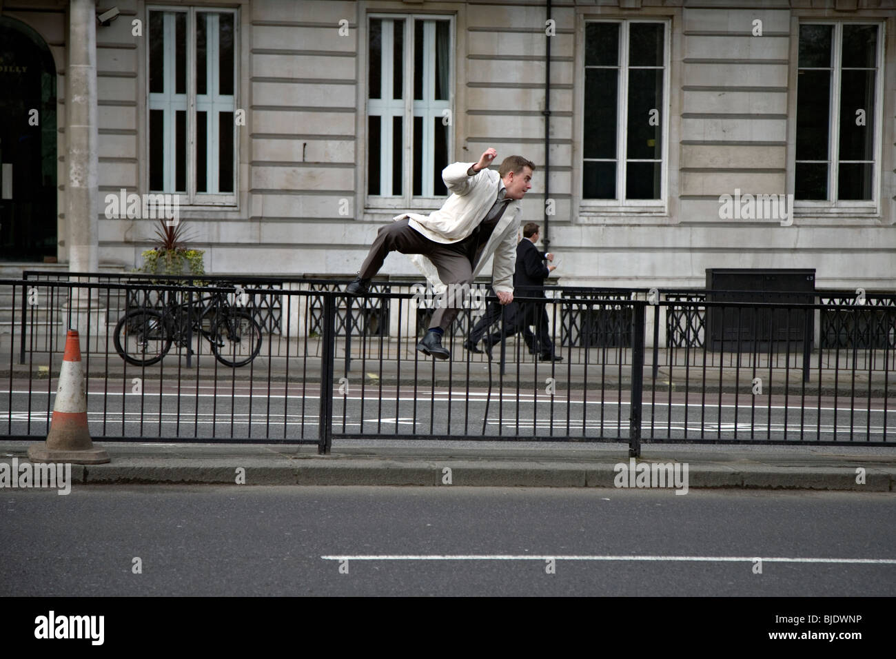 a man jumps a railing on piccadilly london - Stock Image