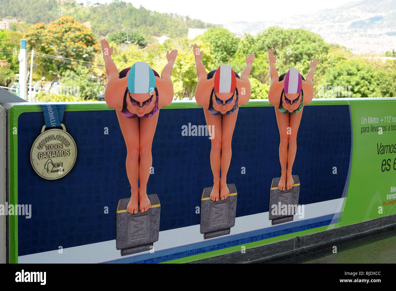 Cardboard cutouts of three swimmers displayed on the metro station platform to promote the South American Games - Stock Image