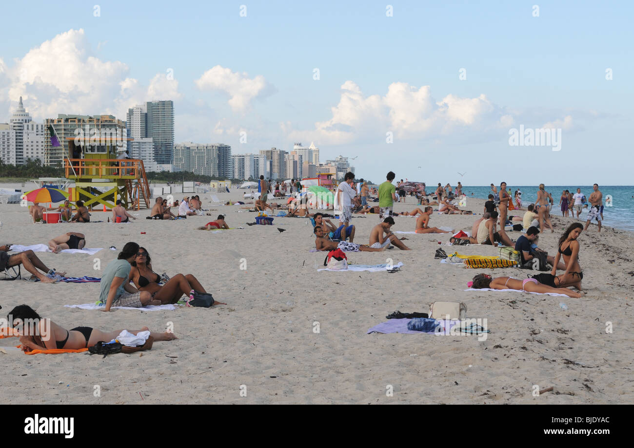 People enyoying the late afternoon sun, sand and warm ocean waters of beautiful South Beach, Miami Beach Florida. - Stock Image