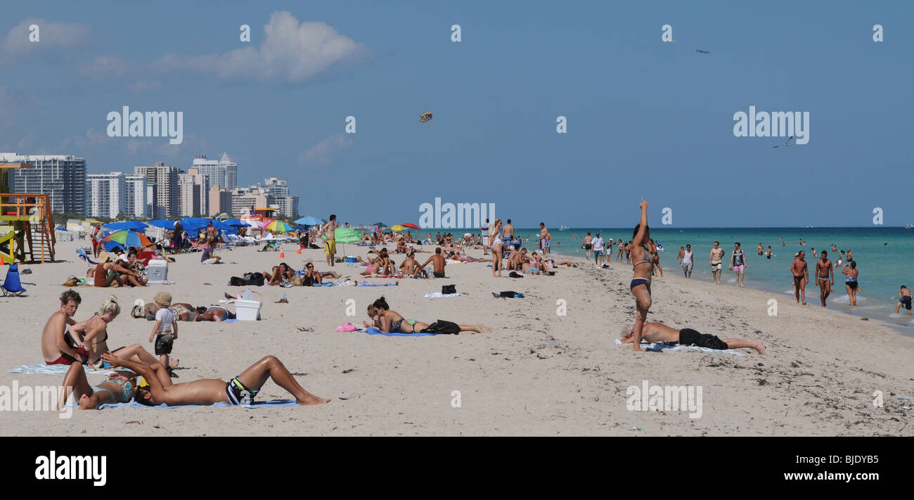 A woman practices yoga, while others enyoy, the sun sand and warm ocean waters of beautiful South Beach, Miami Beach - Stock Image