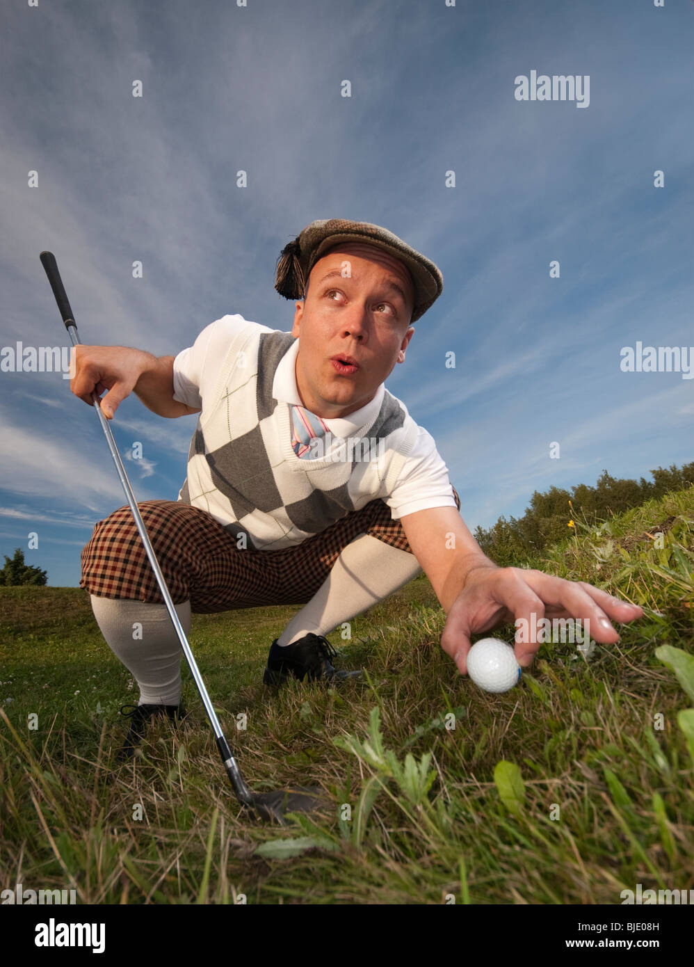 Funny looking golfer cheating and moving the ball when no one sees. - Stock Image
