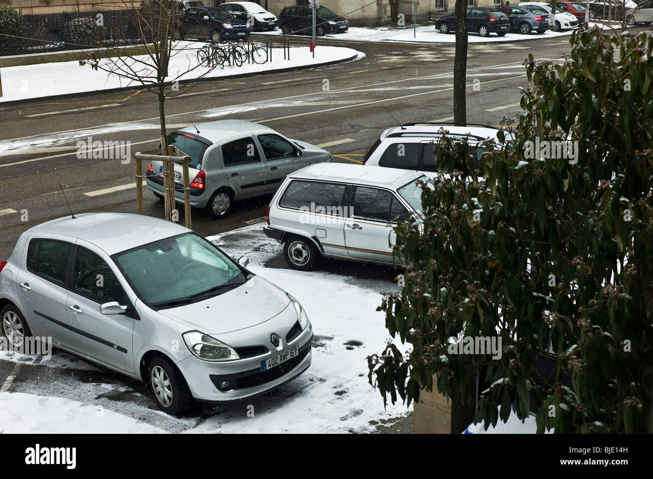 Parked cars on sidewalk with snow, Strasbourg, Alsace, France - Stock Image