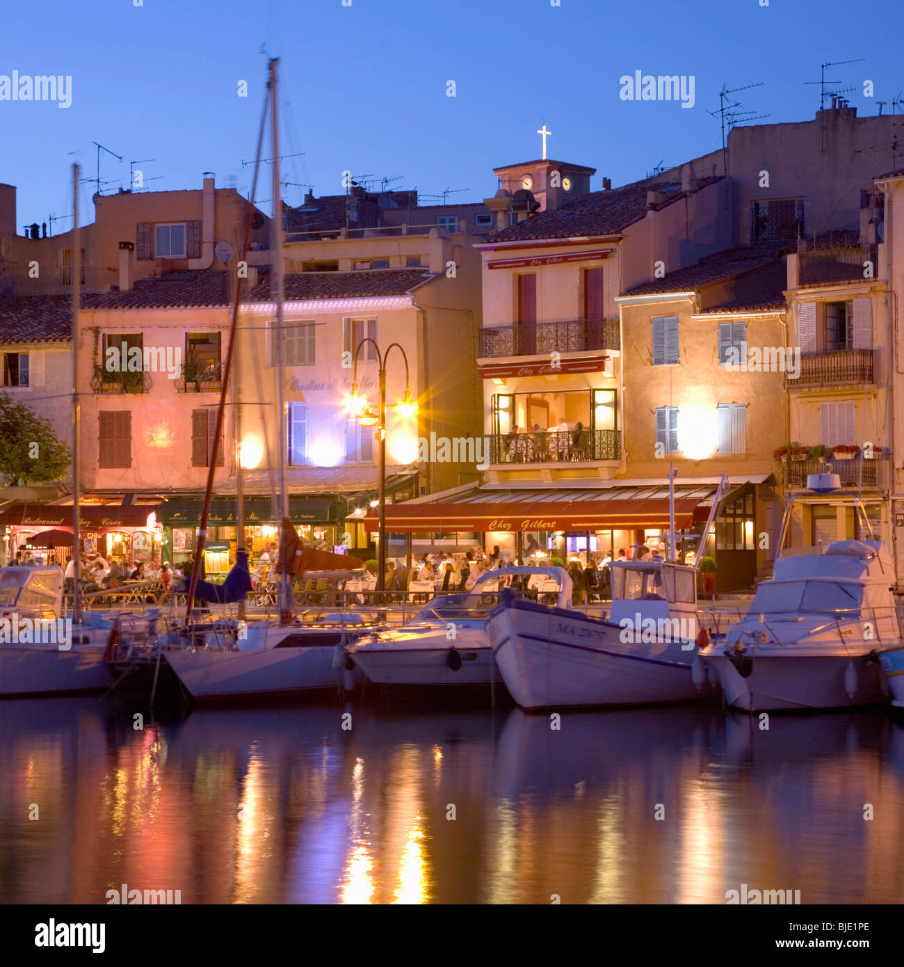 Cassis, Provence, France. View across the illuminated harbour at dusk. - Stock Image