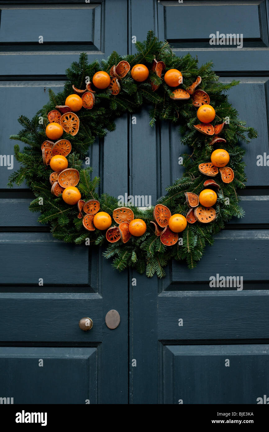 an orange christmas wreath decorating a door at colonial williamsburg at christmas time stock - Williamsburg Decorated For Christmas