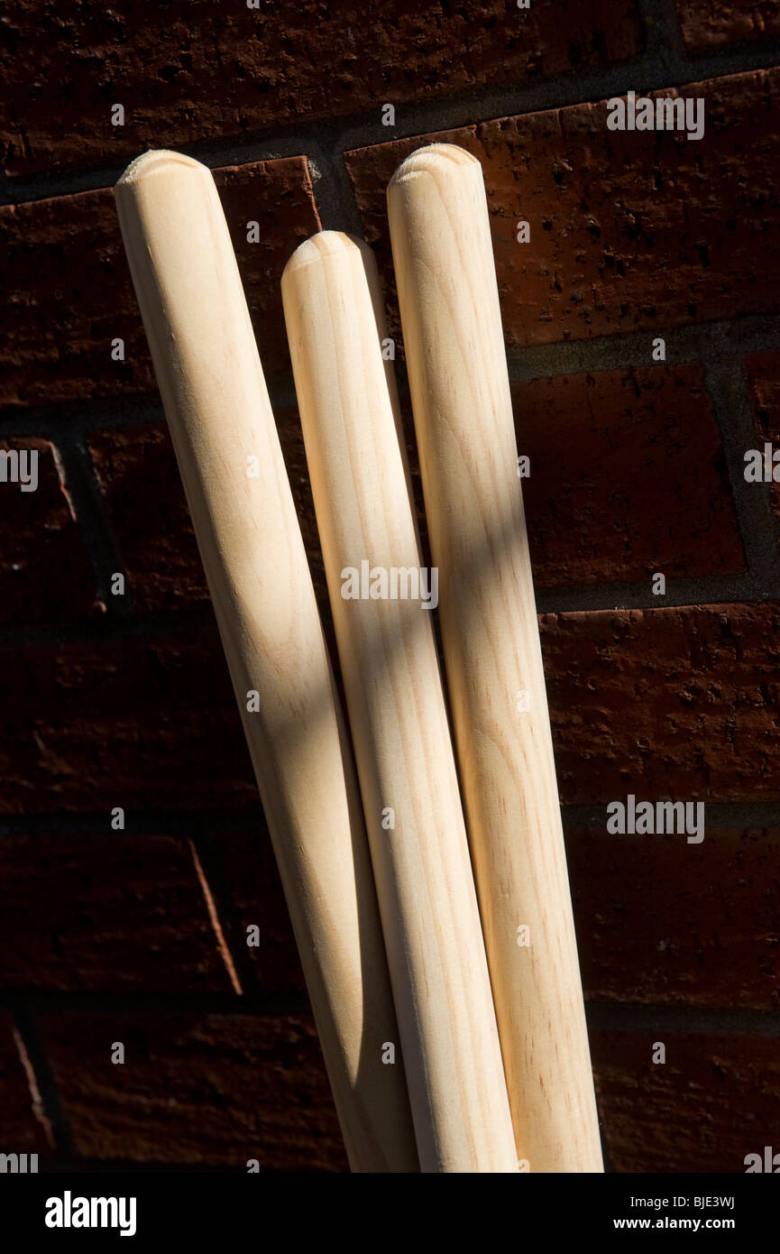 Wooden dowel softwood broom handles propped up against a brick wall outside a hardware shop in Gerrards Cross Buckinghamshire - Stock Image