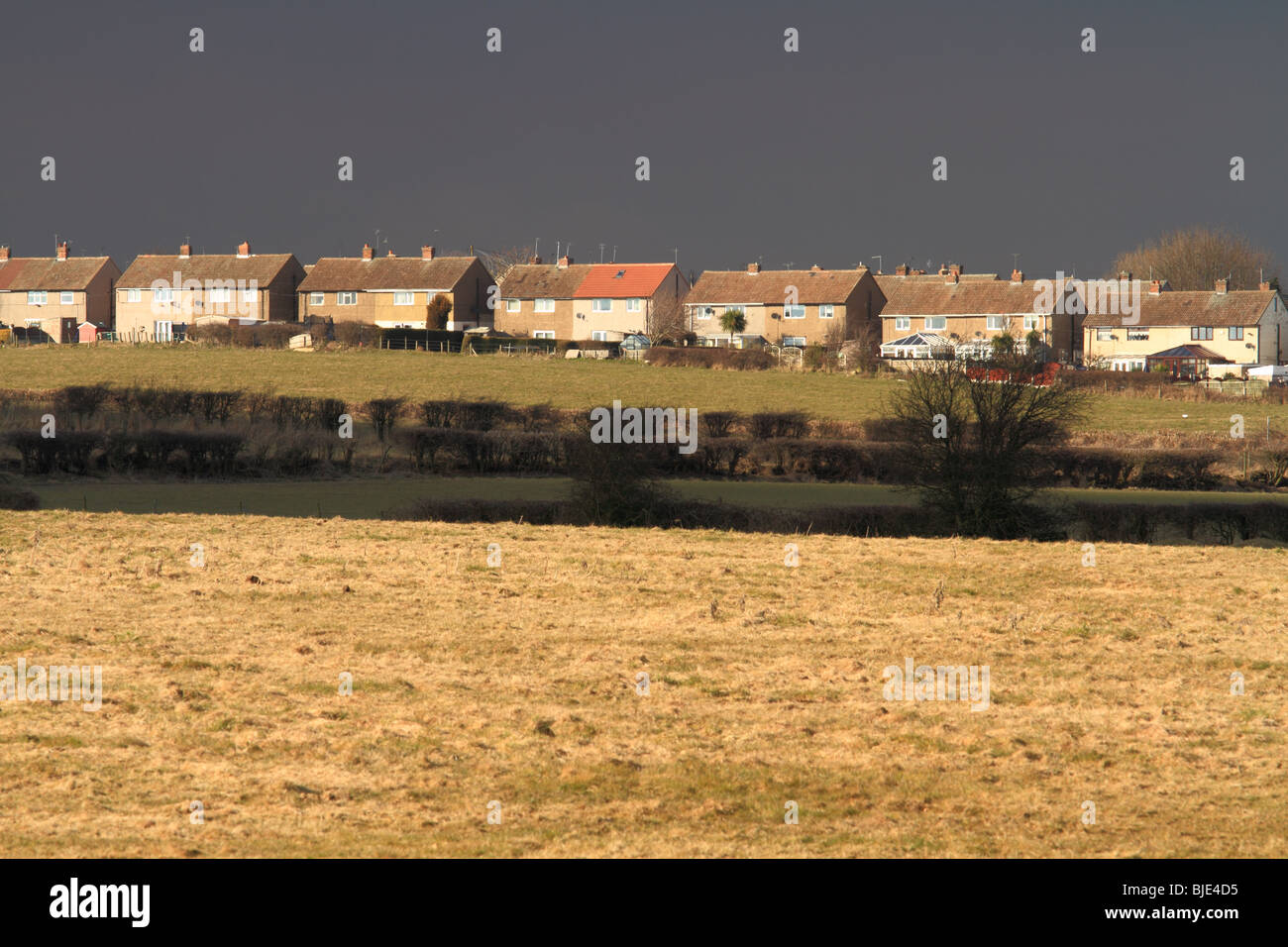 Houses and fields are highlighted by a break in the clouds,prior to stormy weather,across the rooftops of Thurcroft,Rotherham. - Stock Image