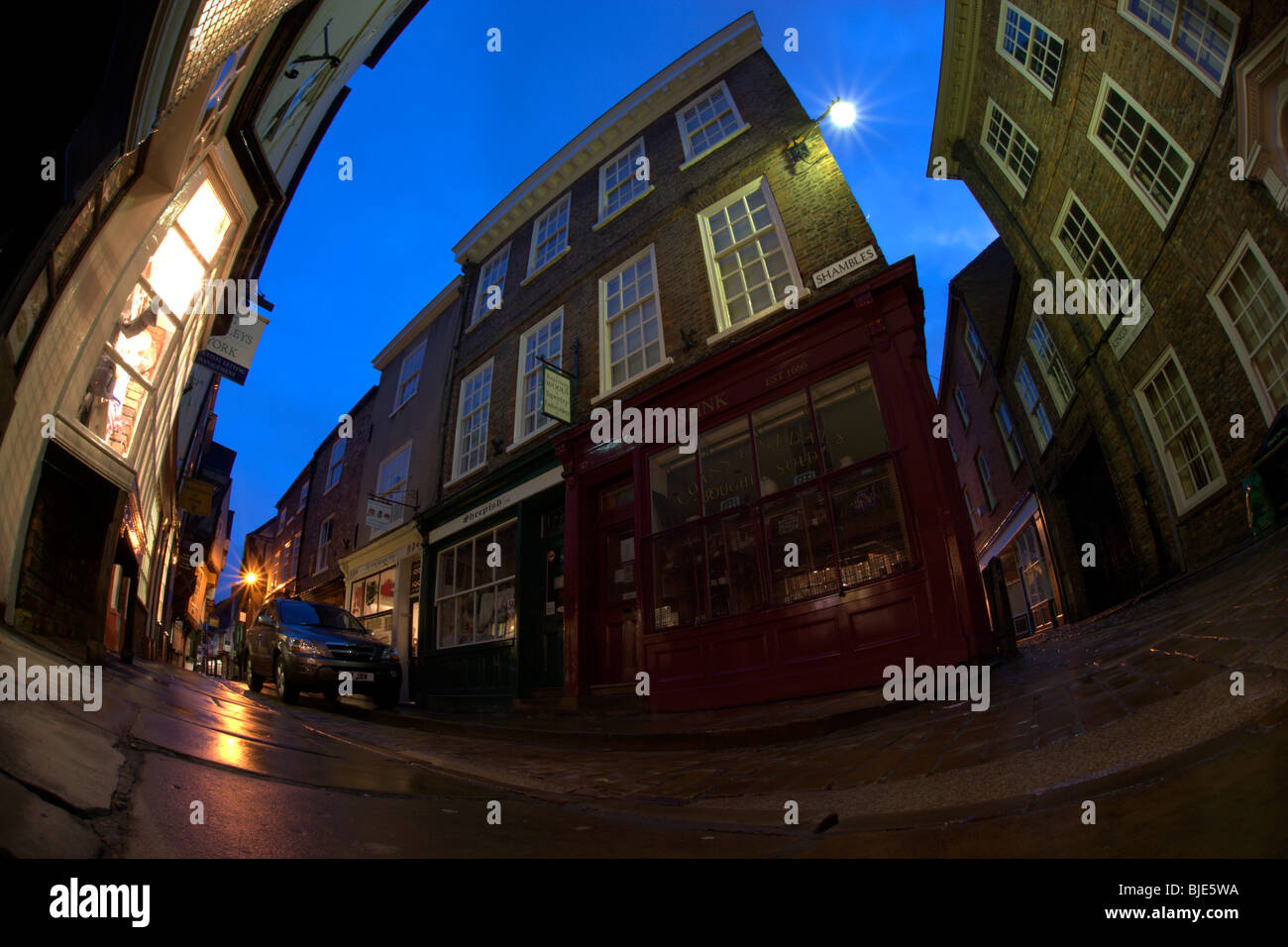 Fisheye view of the Shambles in York at dusk. The pavements are glistening with rain that fell earlier in the day. - Stock Image