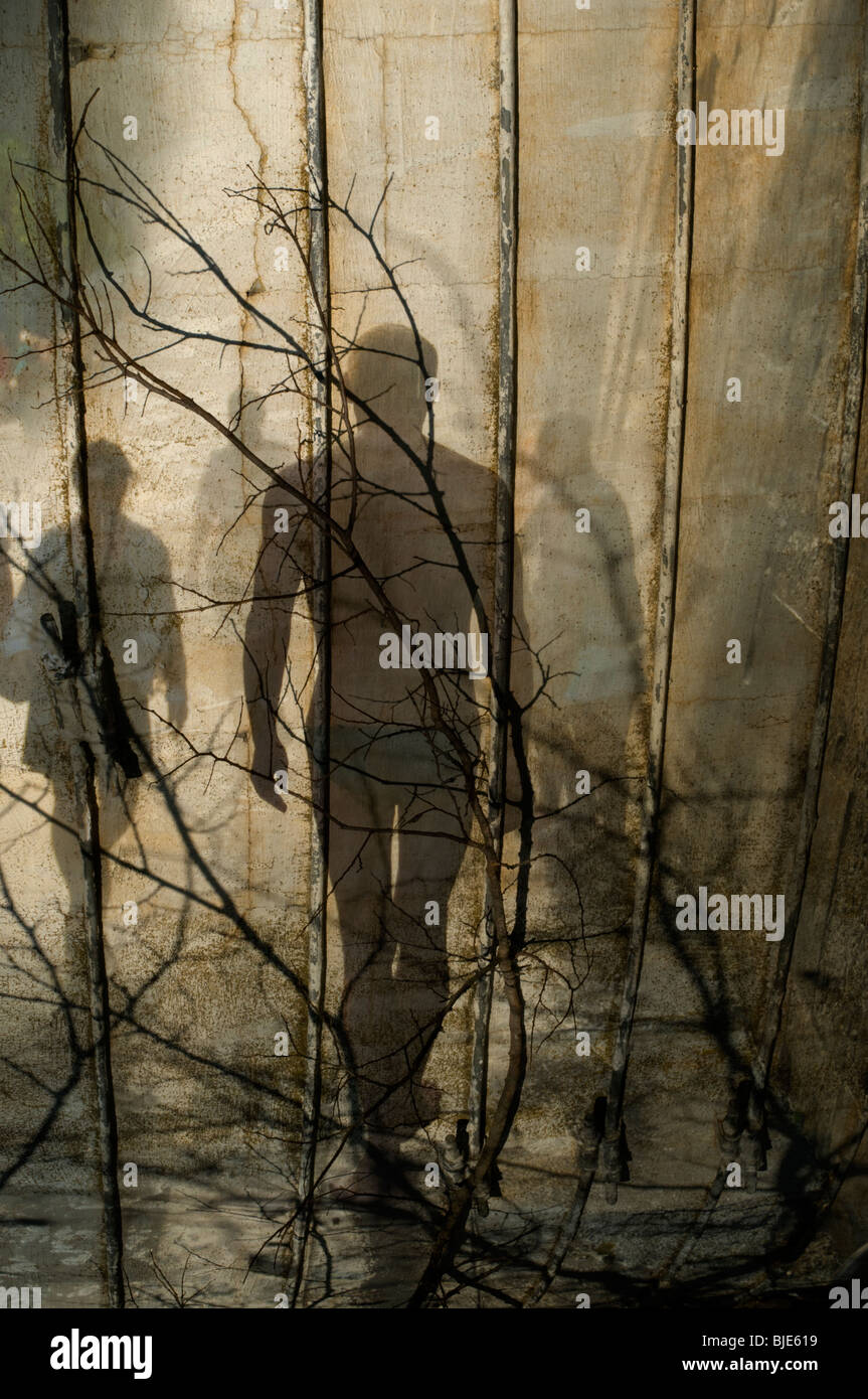 Tree branches looking like barbed wire as shadowy men and women pass in the background Stock Photo