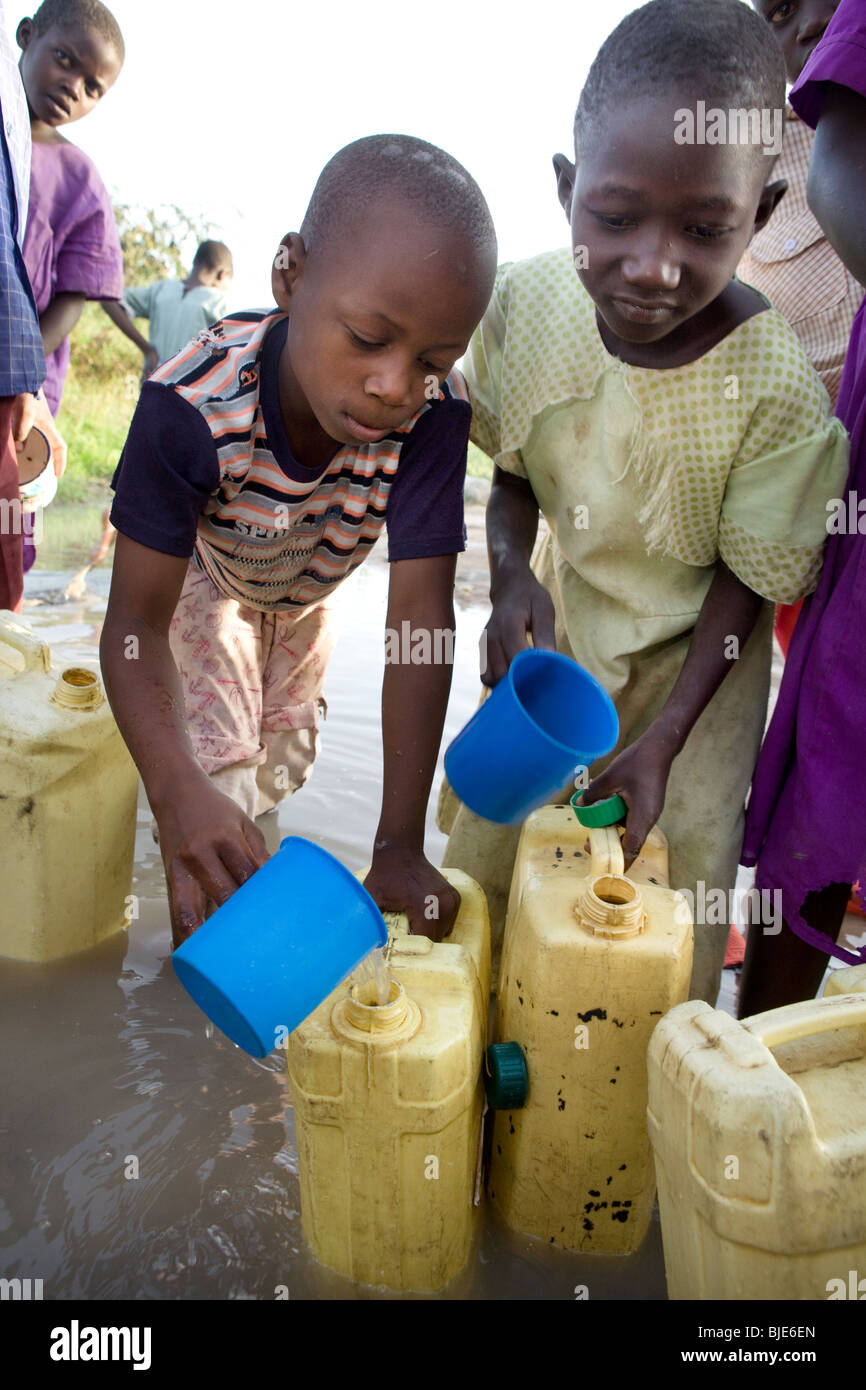 Children draw water from a watering hole in Amuria District, Uganda, East Africa. - Stock Image