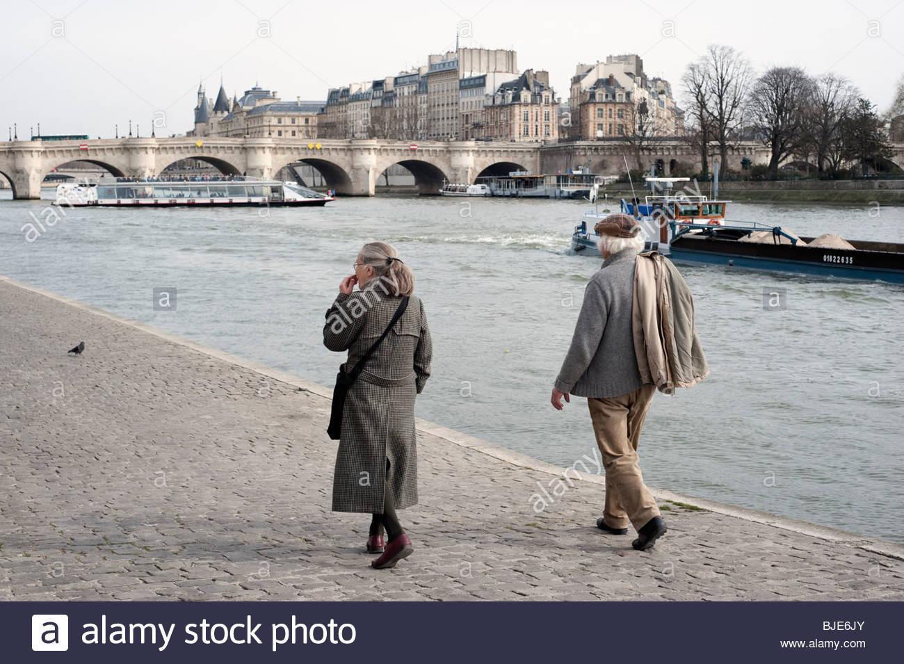 Senior couple walking along Seine river, Paris, France, Stock Photo