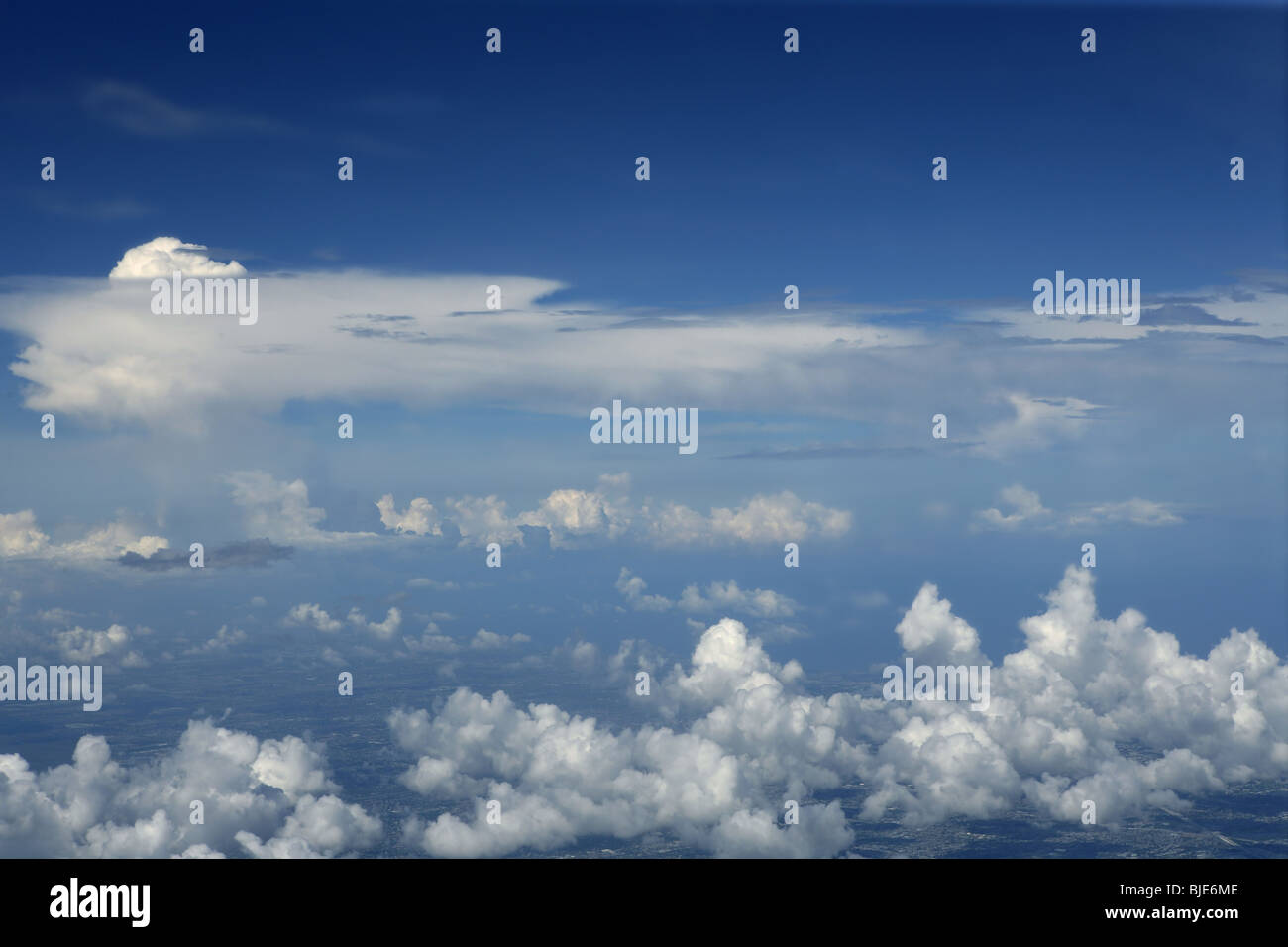 Blue sky view from aircraft airplane and white clouds - Stock Image