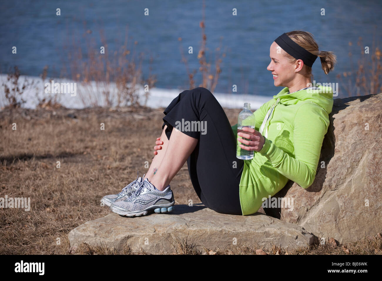 Fit woman relaxing with water bottle Stock Photo