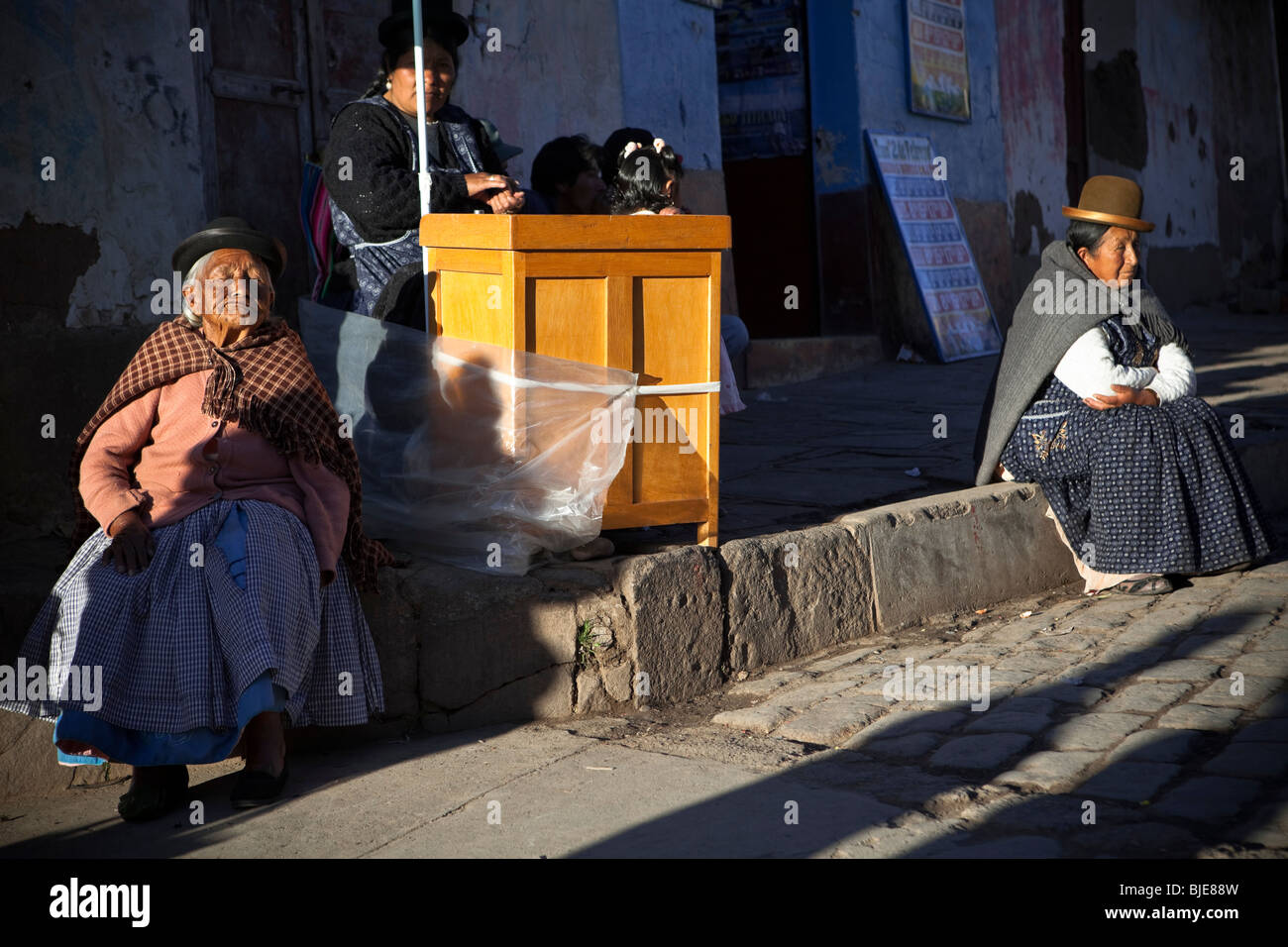 Women in traditional clothes taking sun in a street of Copacabana, Titicaca Lake, Andes, Bolivia South America Stock Photo