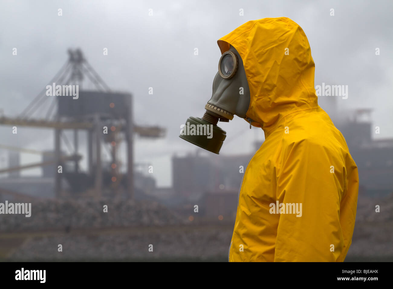 Man wearing gas mask standing in front of factory. Frontal shot. - Stock Image