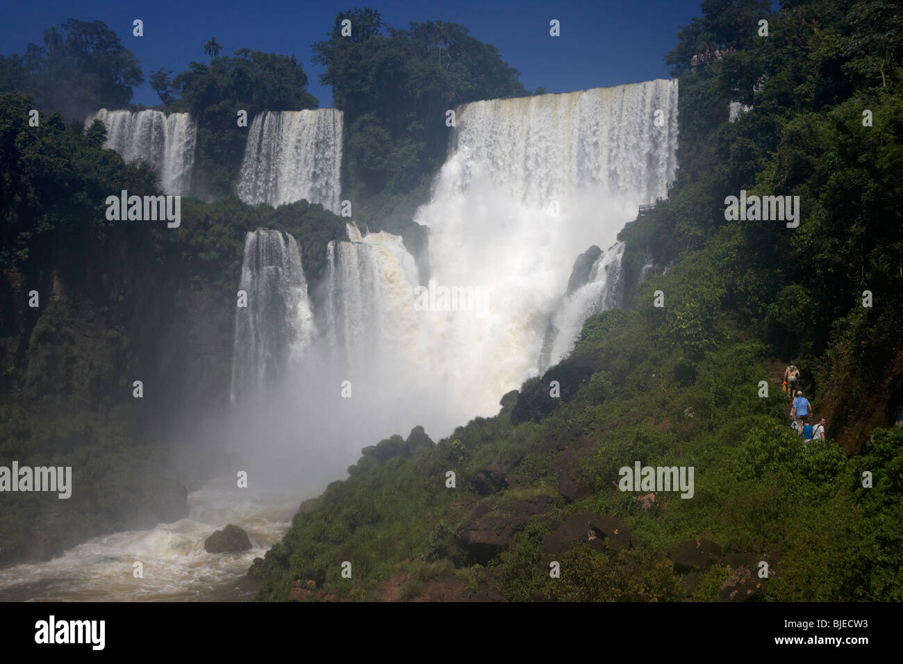 tourists on lower circuit underneath the adan y eva adam and eve fall iguazu national park, republic of argentina, - Stock Image