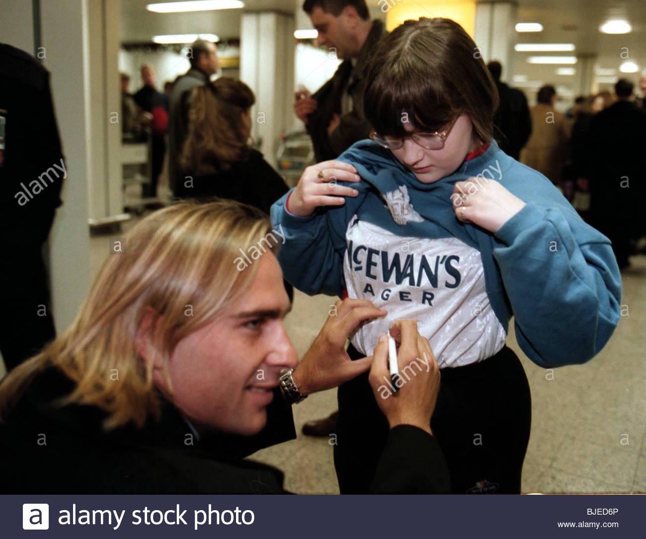 SEASON 1996/1997 GLASGOW AIRPORT New Rangers signing Sebastian Rozental signs the shirt of a young fan. - Stock Image