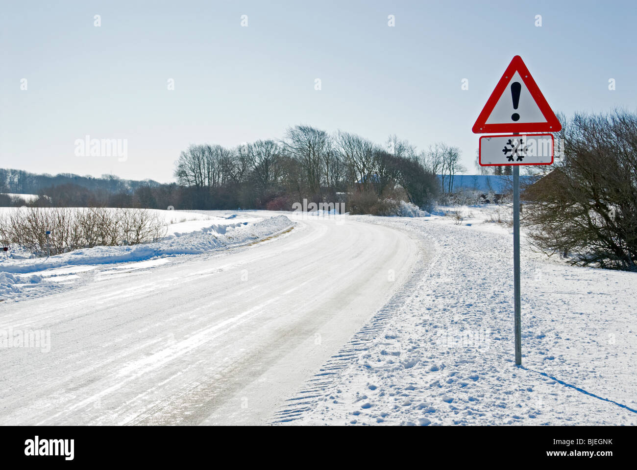 Sign warning for icy and slippery roads. - Stock Image