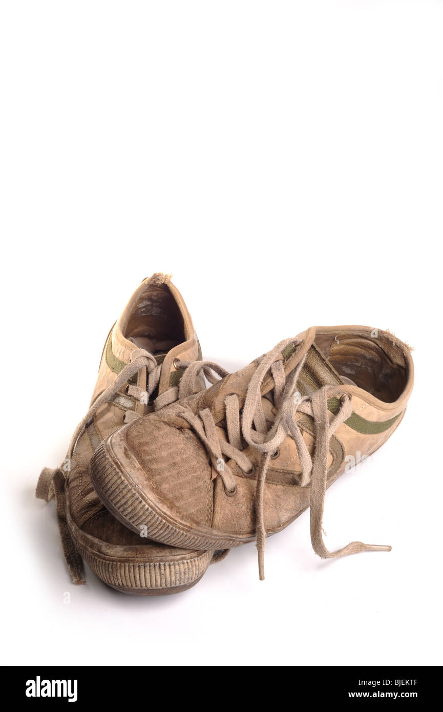 Old Dirty Trainers Photographed against a white background - Stock Image