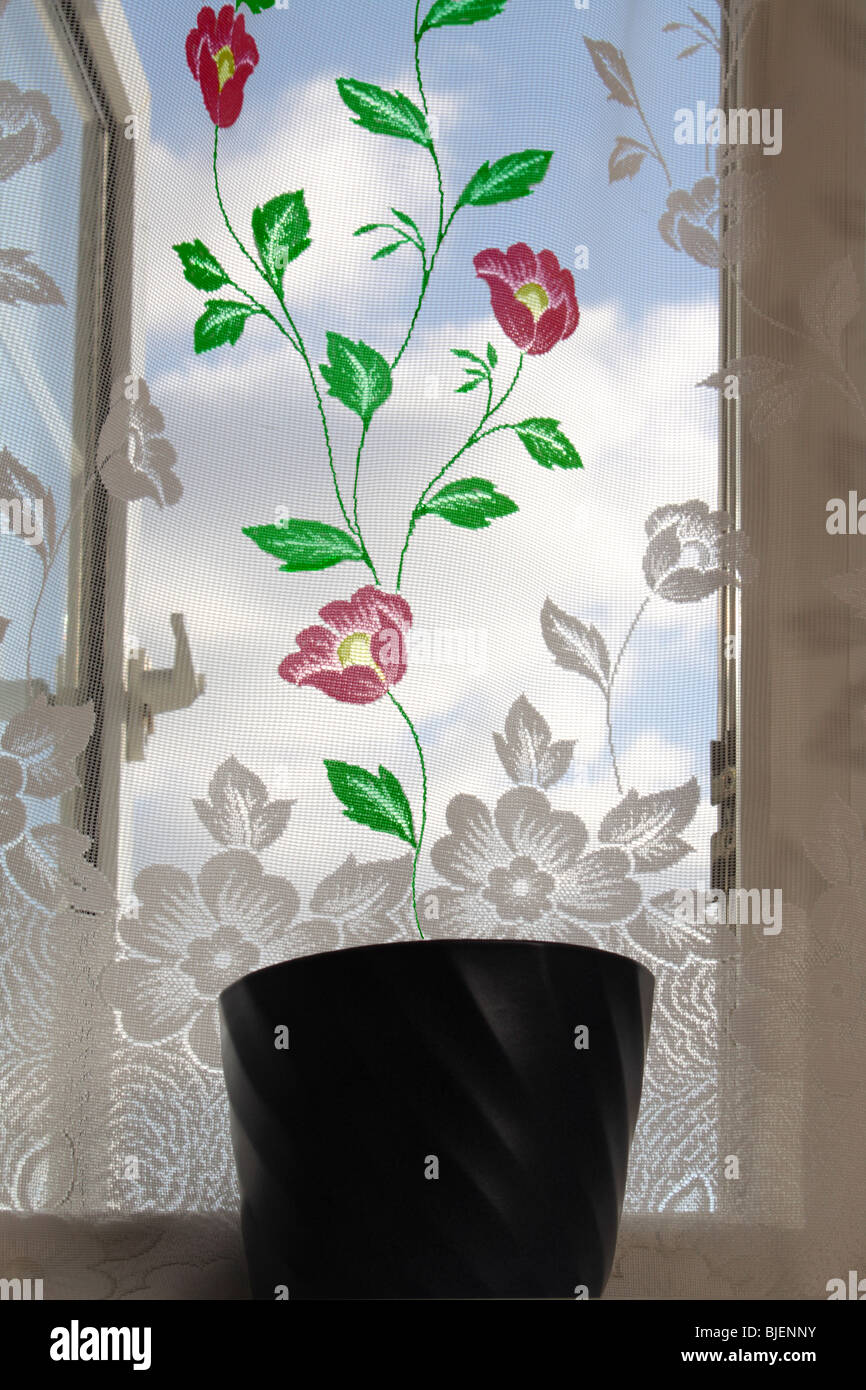 Concept image showing the floral design on net curtains which has been colored to make it look as if it is growing - Stock Image
