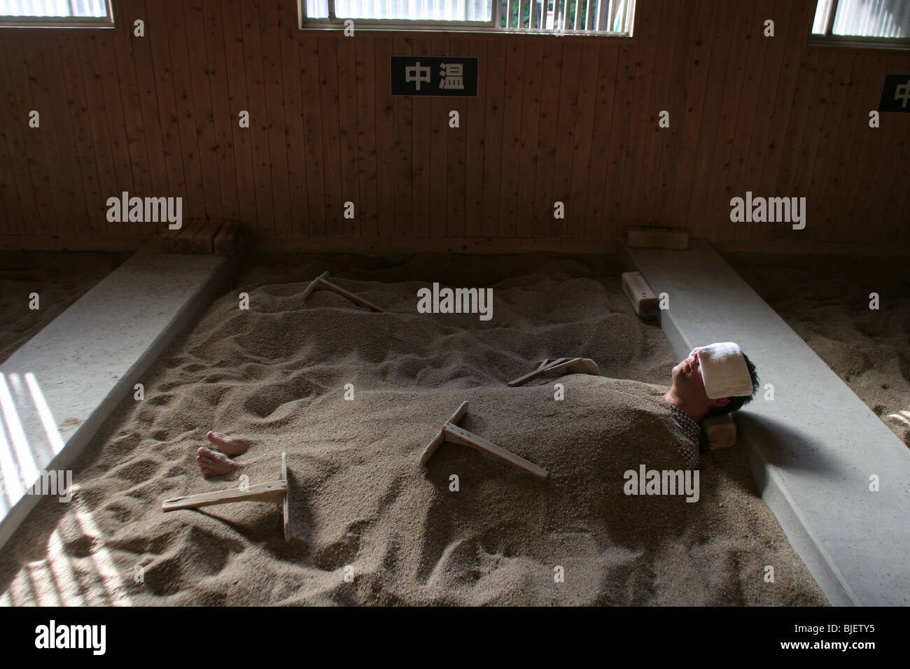 Man takes a sand bath at the 'Hyoten Onsen', Beppu, Japan. 20.10.2005 - Stock Image