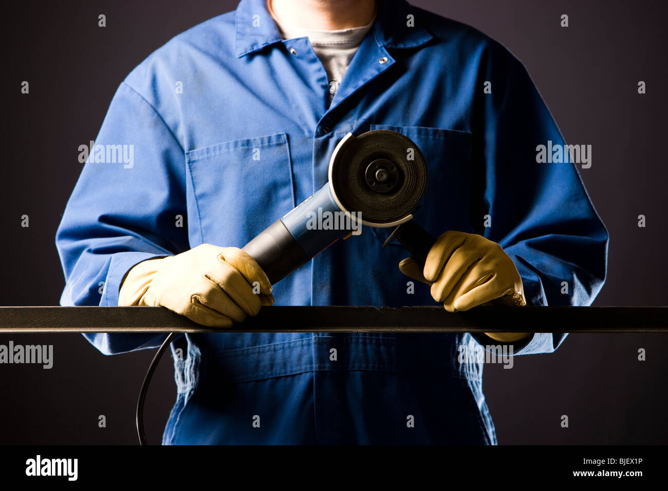 man in blue coveralls with a power grinder - Stock Image