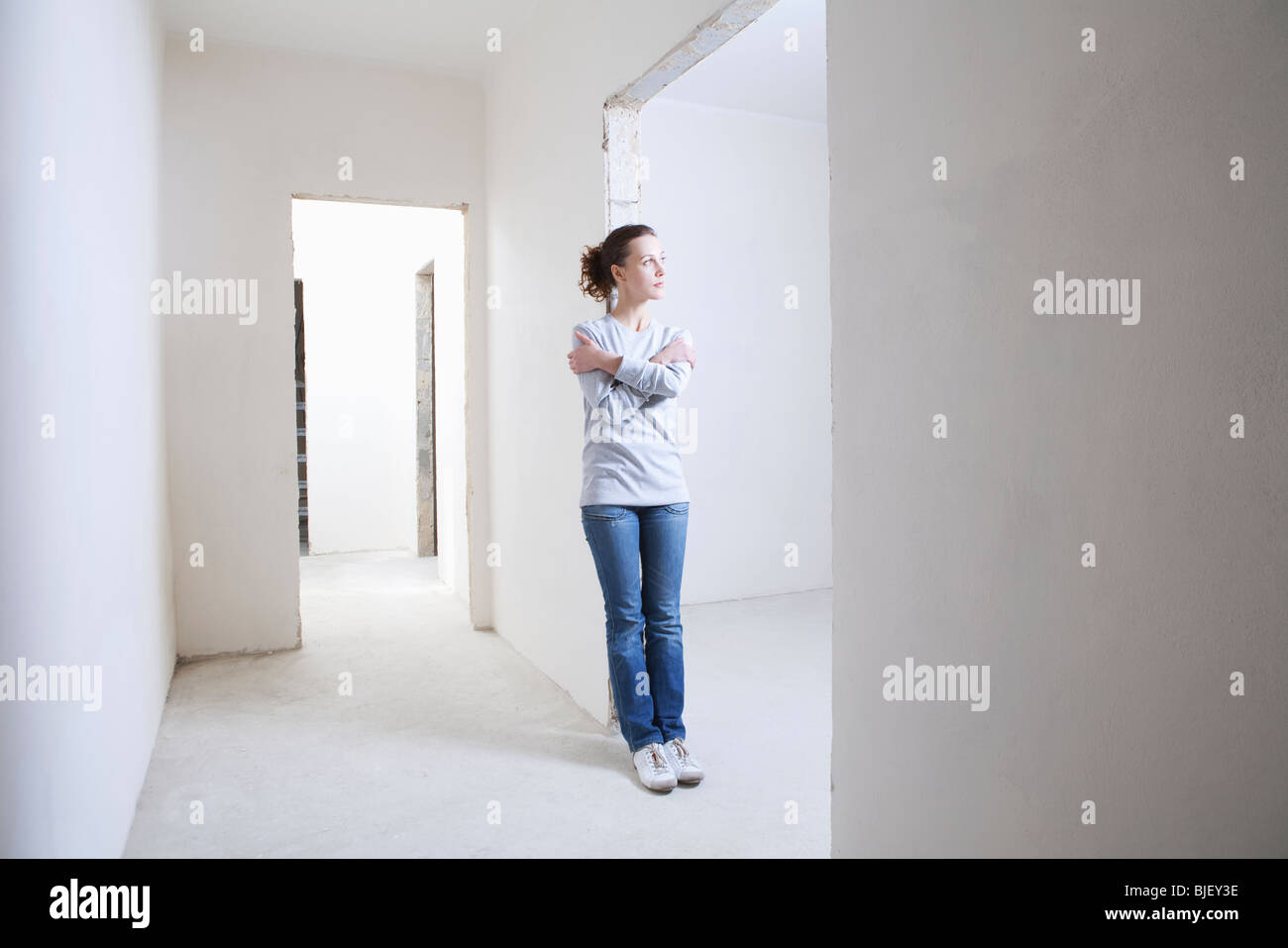 Woman leans on archway of new apartment - Stock Image