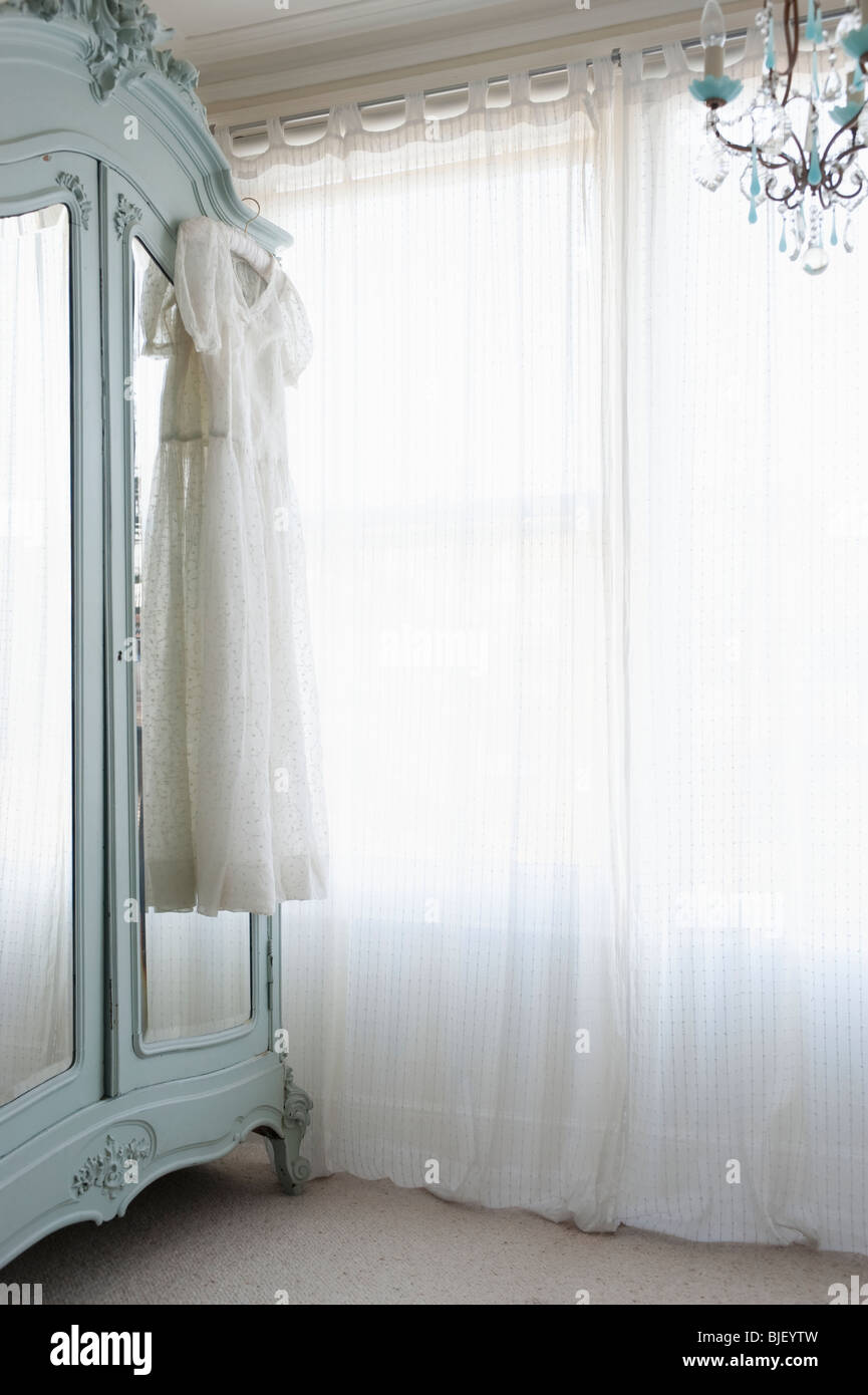 Christening gown on wardrobe at window with net curtains - Stock Image